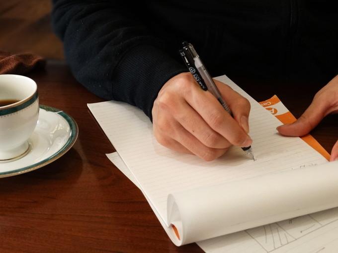 英単語をノートの書いて暗記しているシーン